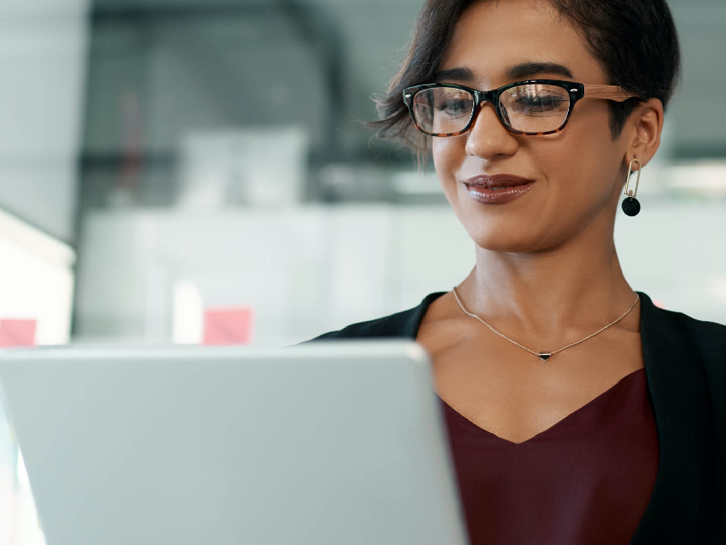 Woman wearing glasses looking at laptop.