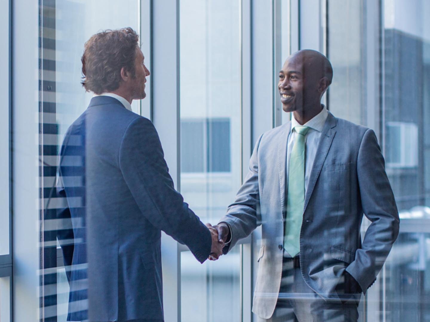 two businessmen shaking hands in office.