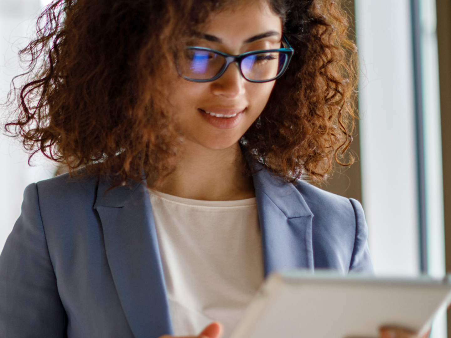 Woman wearing glasses looking at tablet.