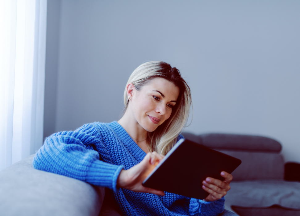 Woman in blue sweater sitting on couch looking at tablet