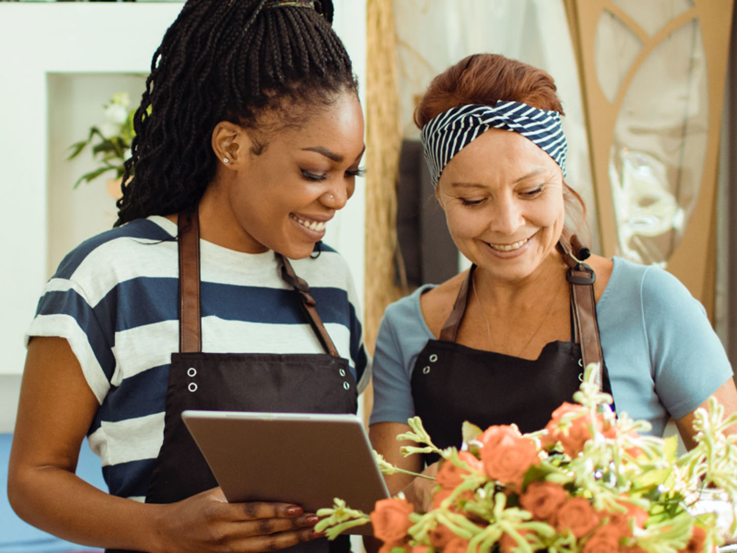 Two women wearing aprons looking at tablet.