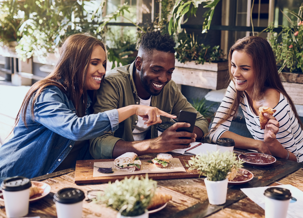 Two women and one man sitting at a table with food with farm chic decor looking at simple checking account on mobile device.