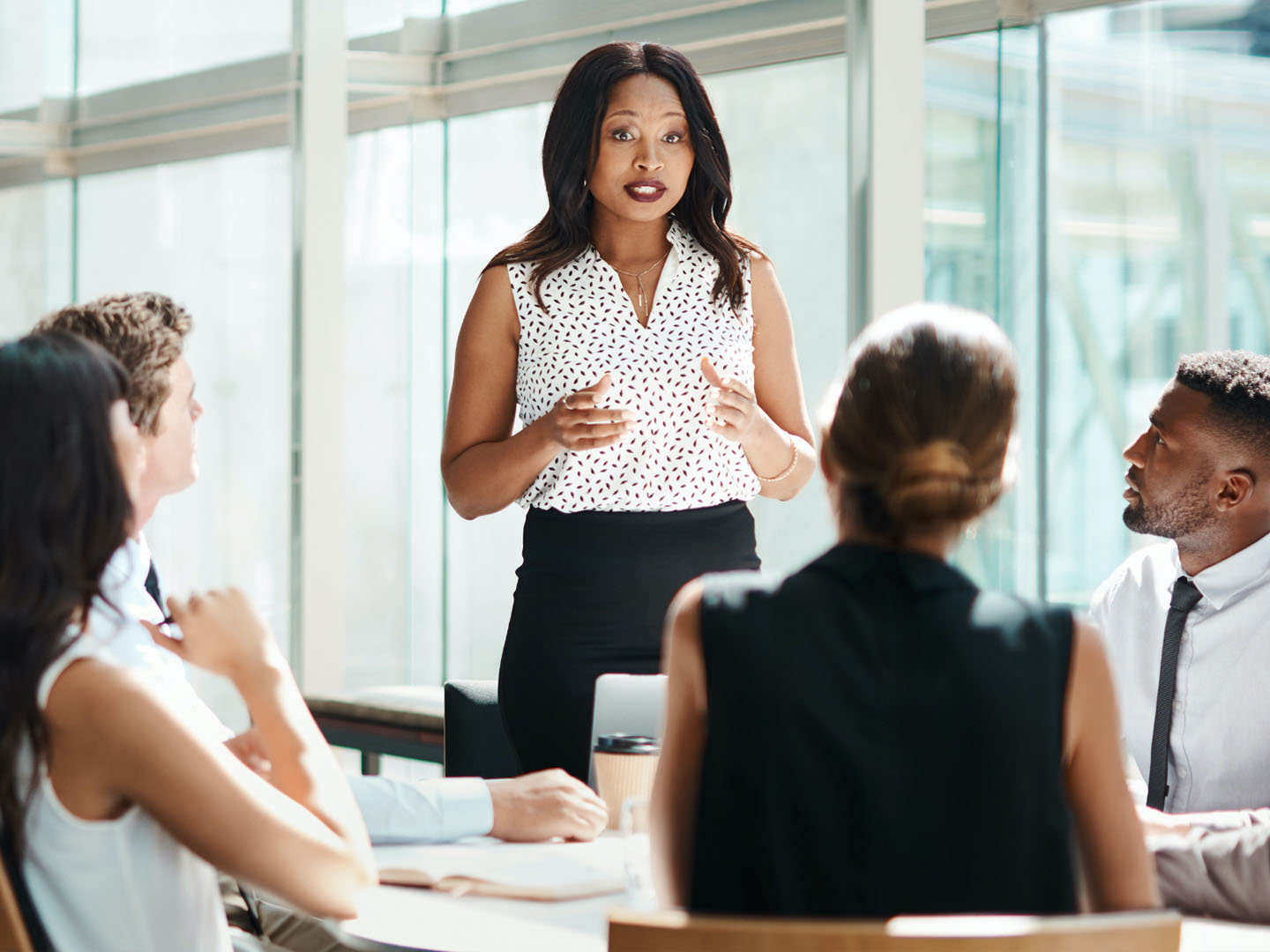 Woman in office discussing ideas with team of four people.