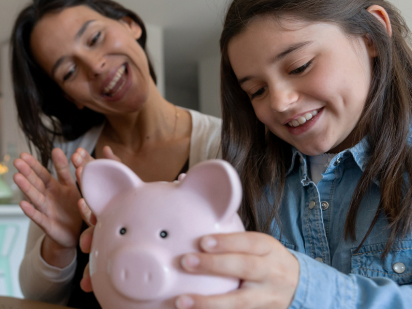 woman and child personal banking pink piggy bank saving money