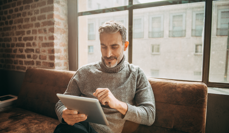 Man sitting on couch looking at tablet