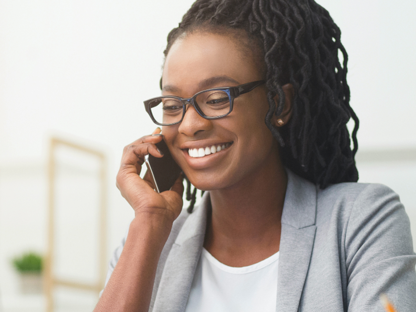 Woman wearing glasses smiling holding mobile phone.