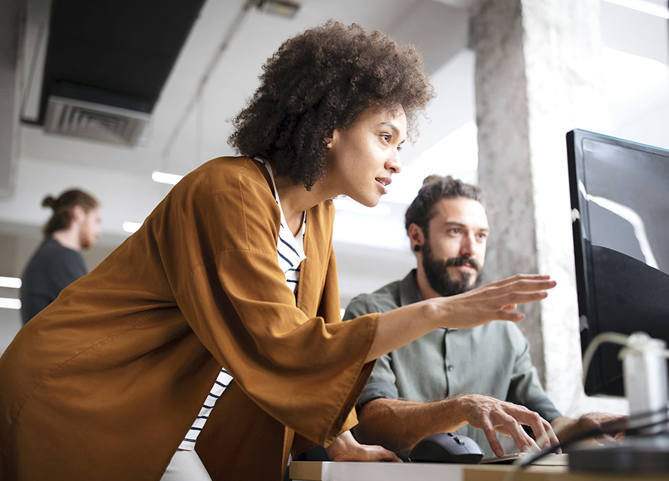 woman and man looking at computer in an office