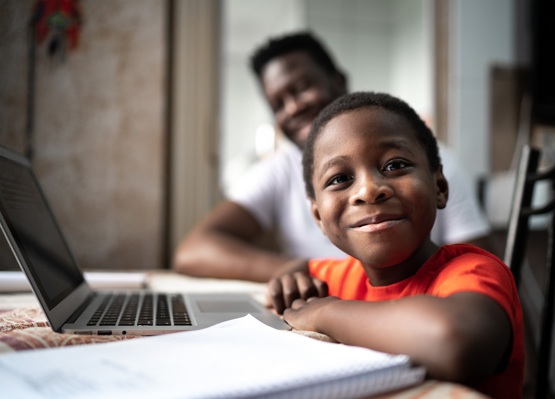 boy sitting at table with dad using computer