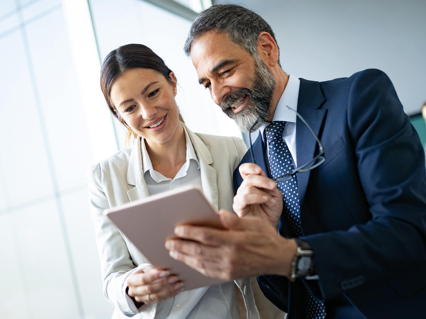 business woman and man looking at tablet in office